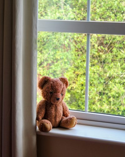 lone-brown-teddy-bear-sitting-on-window-ledge